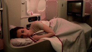 Female passenger sleeping in fully flat bed in new Iberia A330 business class seat
