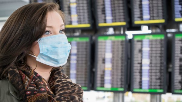 Passenger wears mask at airport (iStock)