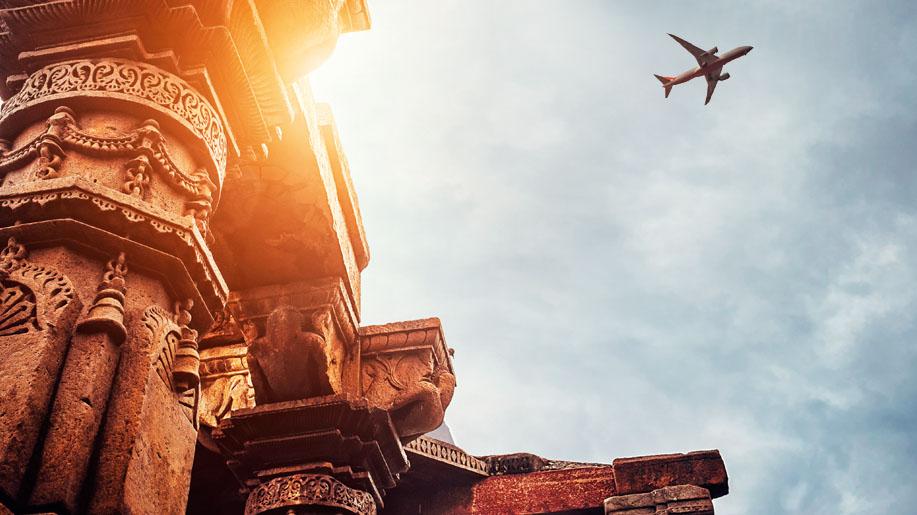 An airplane flies above the Qutb Minar Complex in Delhi