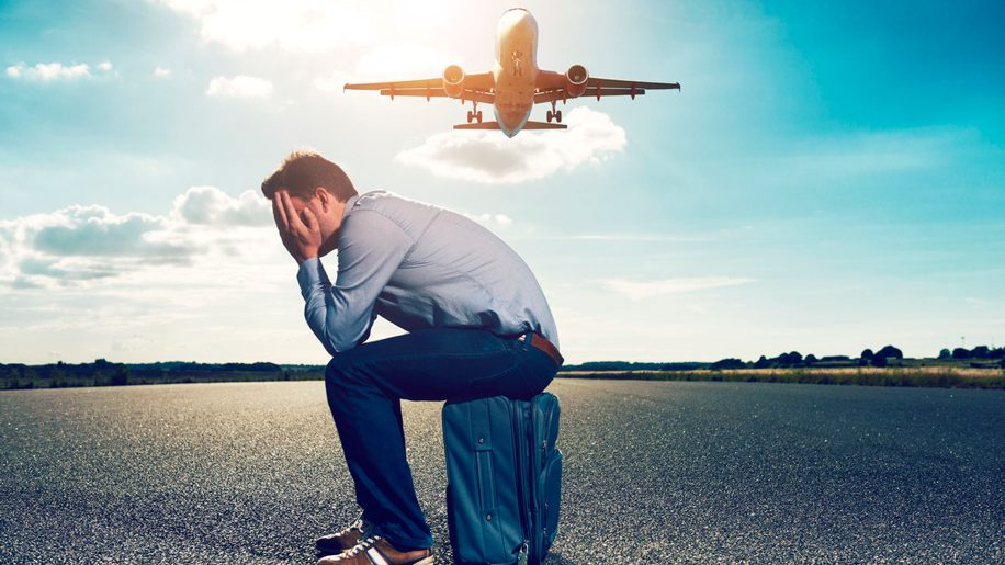 Sad passenger waits with suitcase for plane on runway (iStock)
