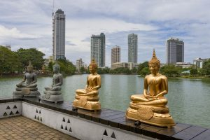 Statues at Gangaramaya Buddhist Temple in front of Colombo's skyscrapers