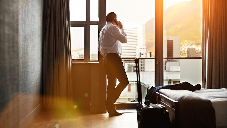 Rearview shot of a businessman looking through a hotel room window and talking on a cellphone